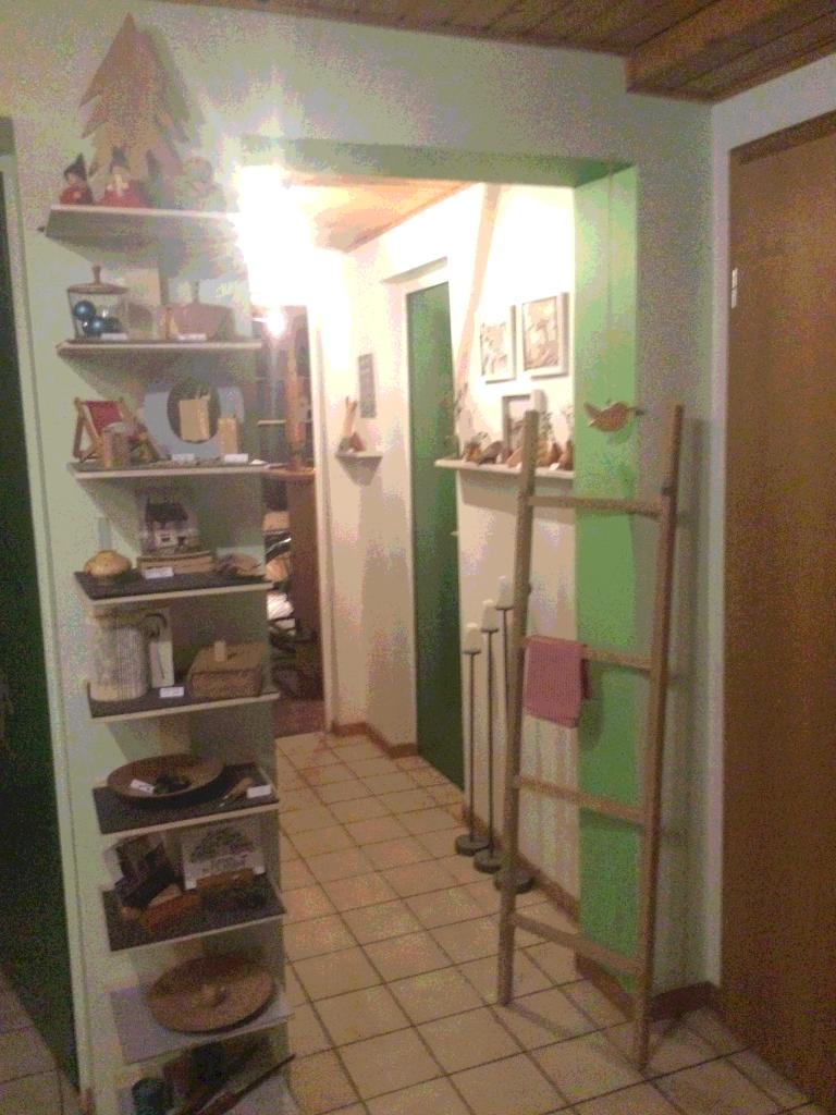 Durchgang in einem Keller, links ein schmales Regal mit Holzprodukten.