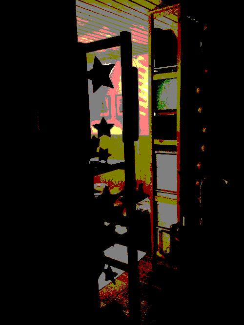 Blick aus dem dunklen Kellergang vorbei an einem Regal, an dem Sterne hängen, hinein in einen hellen Raum voller Sterne und weiterer Produkte aus Holz und Informationen über Sumbawanga