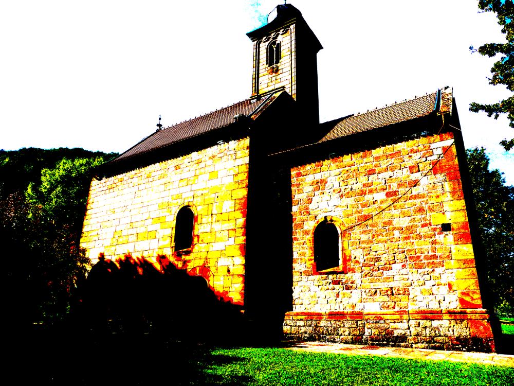 Lorettokirche oberhalb des ehemaligen Klosters Murbach im Elsass. Klobiger Steinbau im Grünen.