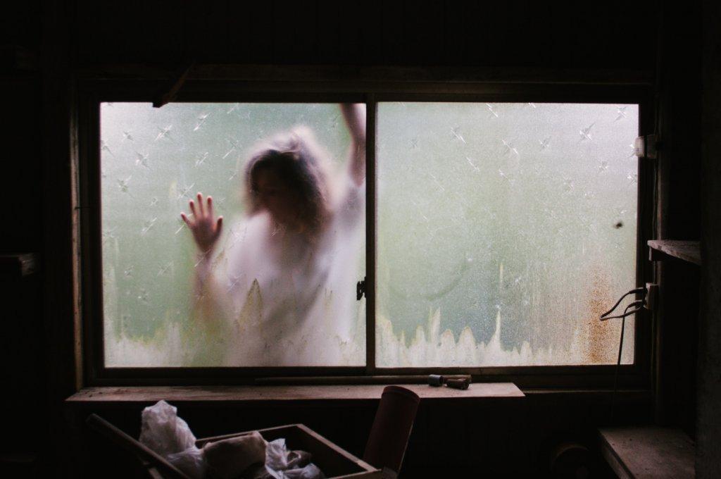 Beschlagenes Fenster. Von außen presst eine Frau dagegen.