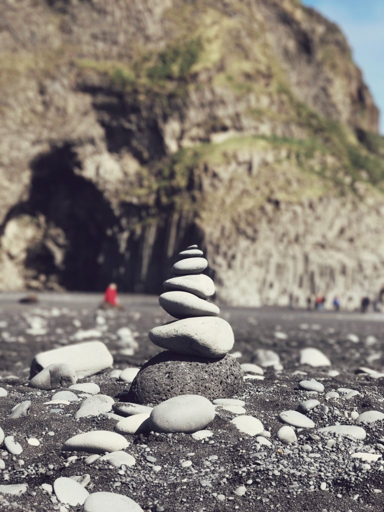 Ein Strand aus schwarzem Sand. Im Vordergrund glatt geschliffene, helle Kiesel übereinander geschichtet. Im Hintergrund ein Mensch, unscharf im roten Pullover. Die Küste ist mit begrüntem Fels zu sehen.