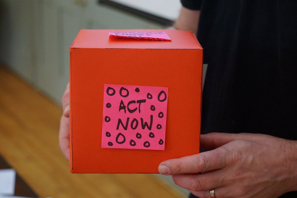 red box in the hands of someone wearing a black shirt, post-it on the box: act now