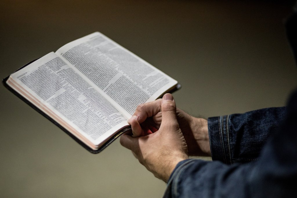 Männerarme schauen aus Jeansärmeln. Die Hände halten unsicher eine Bibel.