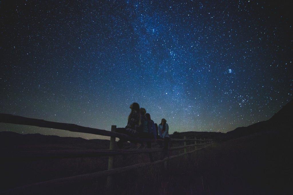 Menschen sitzen nachts auf einem Zaun und schauen in den Sternenhimmel.