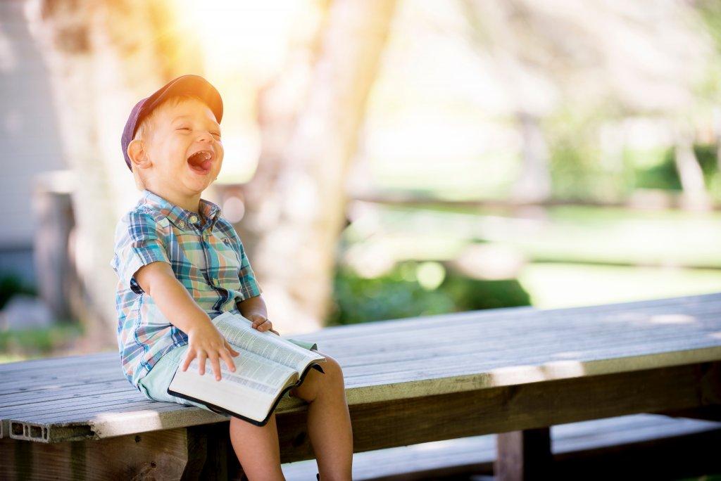 Ein kleiner Junge sitzt lachendauf einem Brett. Er hält mit einer Hand ein aufgeschlagenes Buch auf seinen Knien.
